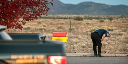Alec Baldwin crouches down in the parking lot outside the Santa Fe County Sheriff's offices after being questioned on the shooting.