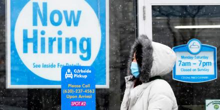 Una mujer pasa por delante de un letrero de que dice Contratando Ahora en una tintorería CD One Price en Schaumburg, Illinois, el 6 de febrero de 2021.