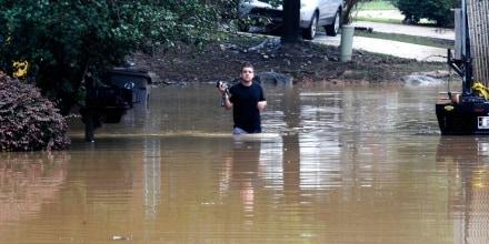 Un vecino trata de hacerse paso en una calle inundada en Pelham, Alabama, el 7 de octubre de 2021, tras las fuertes precipitaciones caídas en el estado.