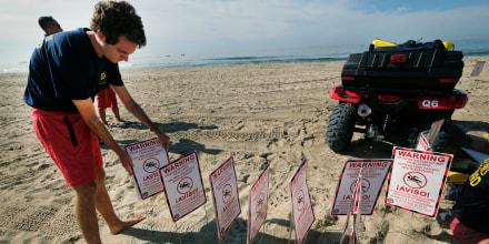 El domingo los socorristas pusieron carteles en Huntington Beach para advertir que el contacto con el agua puede causar enfermedades.