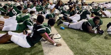 Jugadores se tumban en el campo tras un tiroteo durante el partido de fútbol americano entre Vigor y Williamson en el estadio Ladd-Peebles, en Mobile, Alabama, el 15 de octubre de 2021.