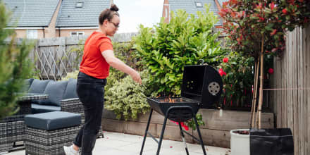 Woman standing over a charcoal grill, grilling. Shop the best charcoal for grilling to use with your charcoal grill. The best grilling charcoal and charcoal tools are from Weber, Royal Oak, Rockwood and more.