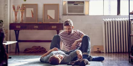 Couple laying on the carpet with their cat, with a window AC unit behind them. These are the best affordable window air conditioners in 2021. Shop the best window air conditioners from LG, GE, Whirlpool, Toshiba and more.