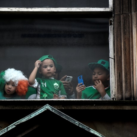 Image: Children watch the St. Patrick's day parade from a window in Dublin