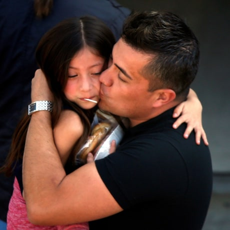 Image: A student who was evacuated after a shooting at North Park Elementary School is embraced after groups of them were reunited with parents waiting at a high school in San Bernardino