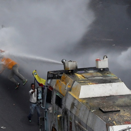 Image: Deputy of the opposition Carlos Paparoni is hit by jets of water during riots at a march to the state Ombudsman's office in Caracas
