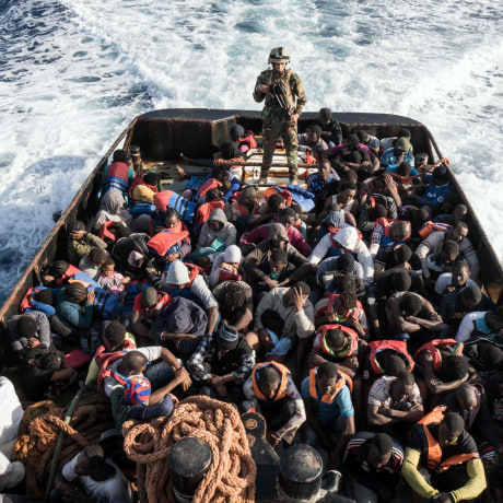Image: A member of the Libyan coast guard stands on a boat as migrants are rescued