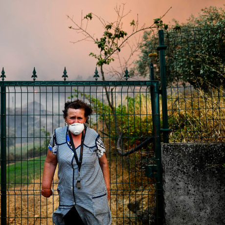 Image: A villager of Sanguinheira stands in front of the gate of her house as a wildfire approaches