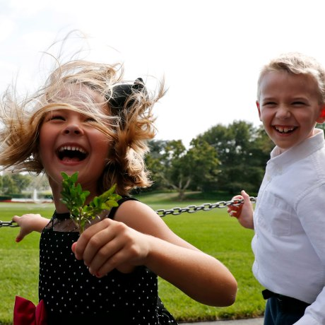 Image: Brooke Fiddes, 5, and her brother Carter Fiddes, 9, both from Charlotte, N.C., react from the rotor wash of Marine One