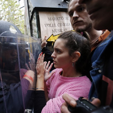 Image: Spanish police push people with a shield outside a polling station in Barcelona