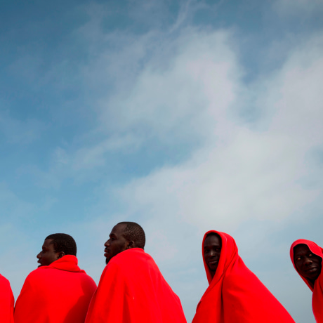 Image: A group of migrants warm up with Red Cross blankets