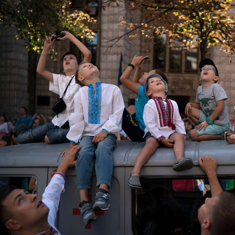 Image: Children look up as aircraft fly above the city center during a military parade to celebrate Independence Day in Kiev