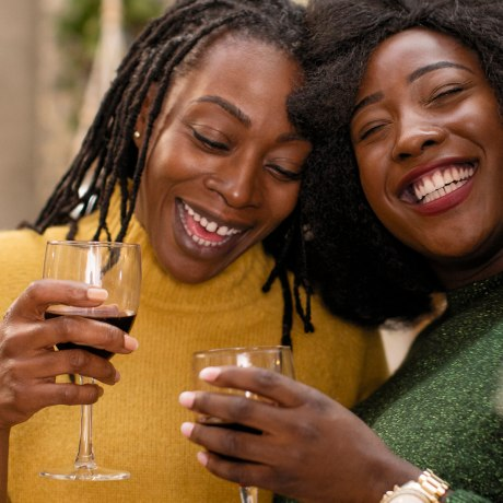 Portrait smiling, happy mother and daughter hugging, drinking wine