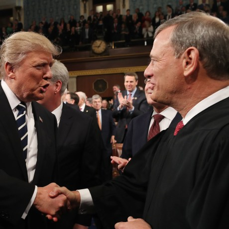 Image: President Donald Trump shakes hands with US Supreme Court Chief Justice John Roberts
