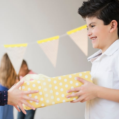 Boy giving girl birthday present at party