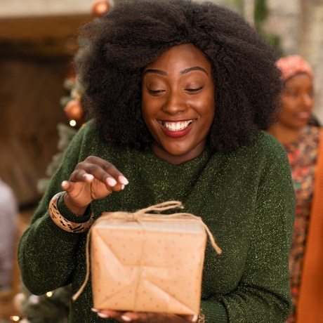 Curious, enthusiastic young woman opening a gift