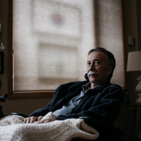 George Gallegos sits at his home.