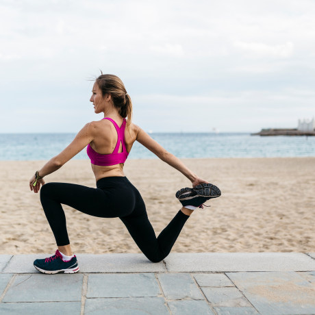 Young woman stretching and warming up for training at the beach