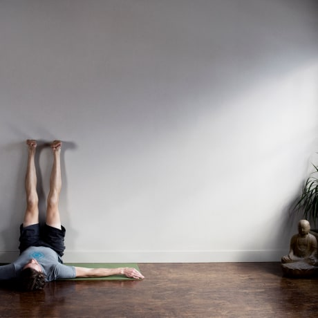 Man lying on floor with his legs stretched out going up wall