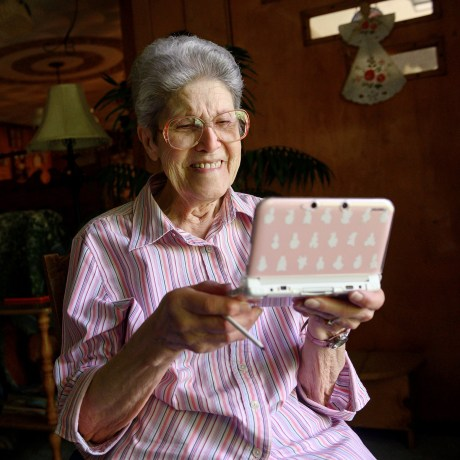 """Image: Audrey Buchanan, 88, plays """"Animal Crossing"""" on her pink Nintendo 3DS XL in her living room at her home in Berlin"""