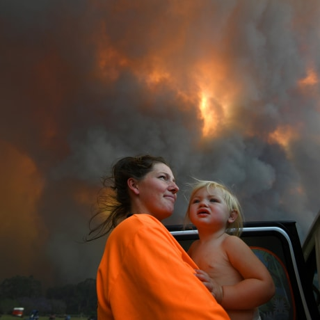 Image: Sharnie Moren and her 18-month-old daughter Charlotte look on as thick smoke rises from bushfires near Nana Glen