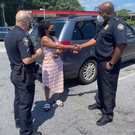 Interim Atlanta Police Chief Rodney Bryant shakes hands with a woman who received a gift card for groceries, courtesy of Tyler Perry.