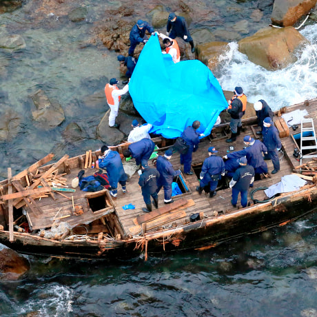 Police officers investigate a wooden boat marked with Hangul characters on Sado island, Niigata prefecture