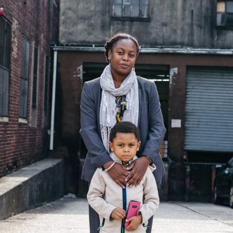 Melissa Miles with son Kiluan in front of the plastics factory in Newark's Ironbound neighborhood.