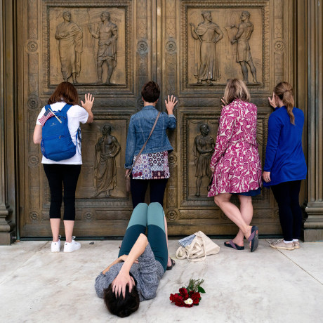 Image: Conservative women who support Judge Amy Coney Barrett's nomination to the Supreme Court, pray while touching the doors of the Supreme Court in Washington as Jacquelyn Booth lays on the ground mourning the death of Justice Ruth Bader Ginsburg on Sa