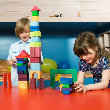 Boy and girl (6-9) at table playing with building blocks, smiling