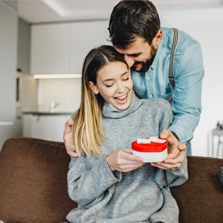 Image: Young romantic couple holding present