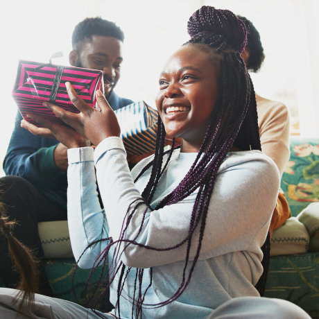 Low angle view of excited girl holding  present while sitting with sister in living room