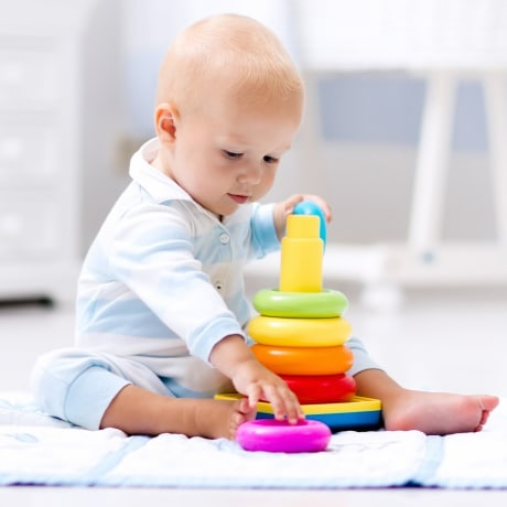 Cute baby playing with colorful rainbow toy pyramid sitting on play mat in white sunny bedroom.
