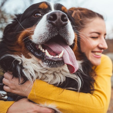Woman hugging her dog outside