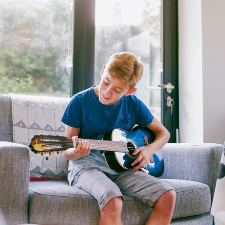 14 year old boy playing on a guitar he got as a gift