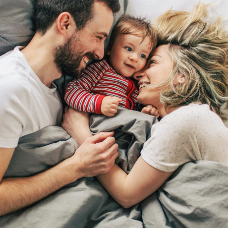 Mom and dad hugging their baby in bed, under the blanket