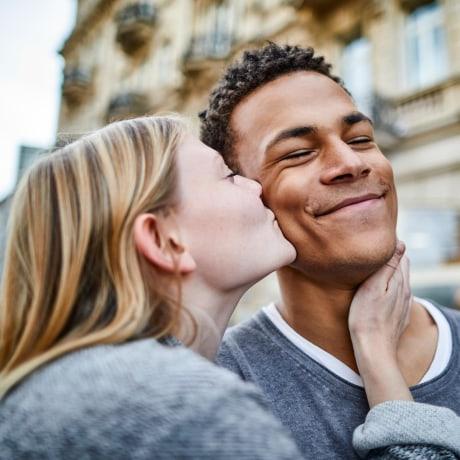 Wife kissing her husband on the cheek outside