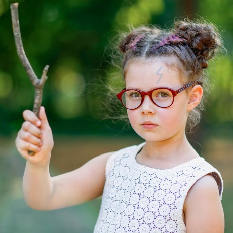 Little girl in red glasses, holding a stick, pretending it is a wand, with a Harry Potter scar on her forehead
