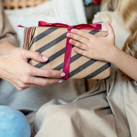 Woman handing her daughter a box wrapped in striped black and brown wrapping paper and a red ribbon