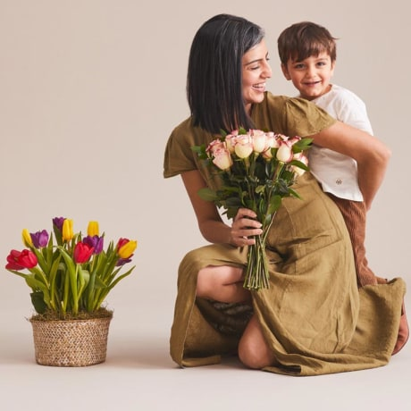Image of a Mother and little son hugging, holding flowers