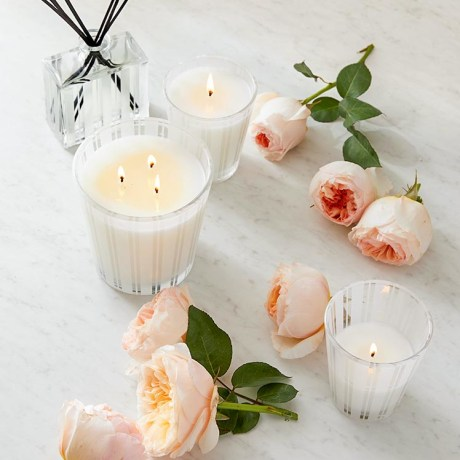 White candles surround by roses