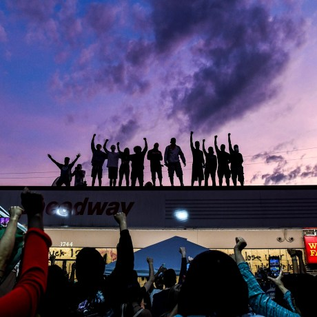 Image: People raise their hands in protest at a memorial for George Floyd in Minneapolis on June 2, 2020.