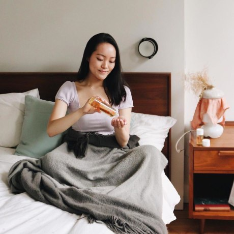 Image of a Woman putting Bio-Oil in her hand and a hand holding Bio-Oil