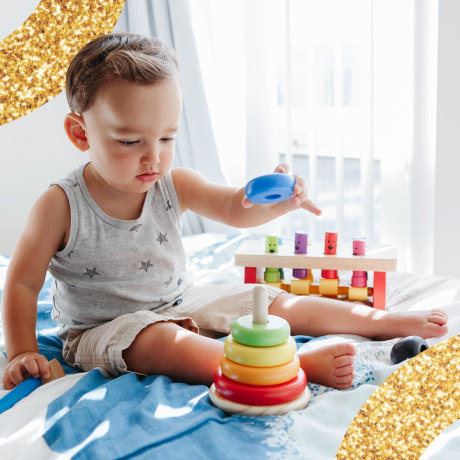 Toddler Playing With Learning Toy Pyramid Stacking Blocks At Home