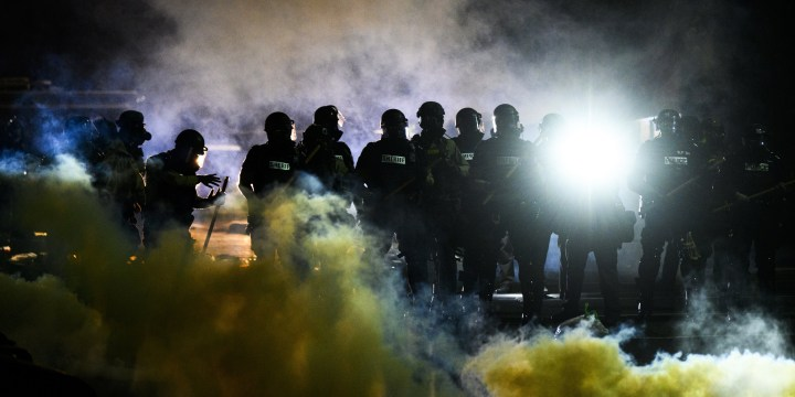 Tear gas fills the air as people confront police outside the Brooklyn Center police headquarters on April 11, 2021, in Brooklyn Center, Minn.