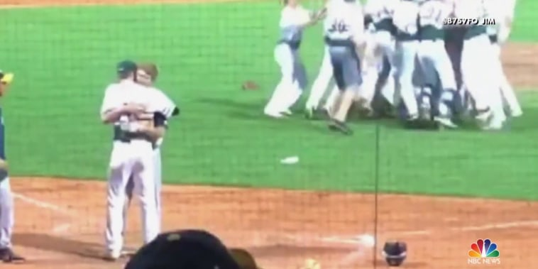 After winning high school baseball game, player hugs friend on opposing team