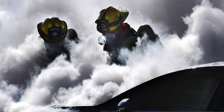 Firefighters are partially obscured by smoke, Nov. 11, 2014, as they work to extinguish a burning car in Salina, Kan.