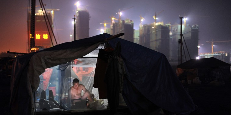 A worker uses a laptop inside his dormitory near a residential construction site in Hefei