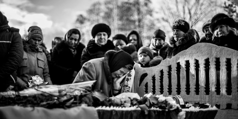 The mother of Private Oleg Yandiuk, 23, member of the 26 Artillery Battalion and killed in combat against DNR forces, cries over the body of her son during his funeral in Turchinka, about 100 miles north of Kiev, Ukraine, Jan. 10, 2015.