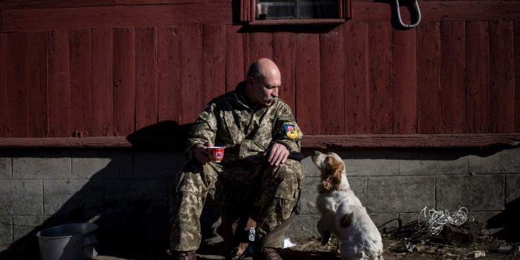 Vasily Yakovenko, captain of a Ukrainian military medical unit, pats a dog near the village of Luhanske, eastern Ukraine, Feb. 24, 2015.  Ukrainian officials...